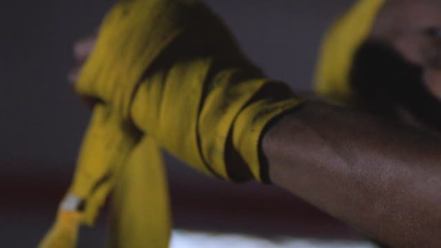 slo mo. cu. boxer wraps his hands with yellow wrapping tape before a fight in a professional boxing gym - bandage stock videos & royalty-free footage