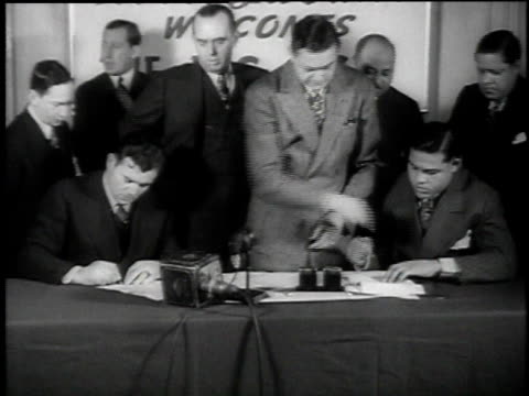 boxers james braddock and joe louis posing for cameras and signing contracts together for a championship fight / united states - 1937 stock videos and b-roll footage