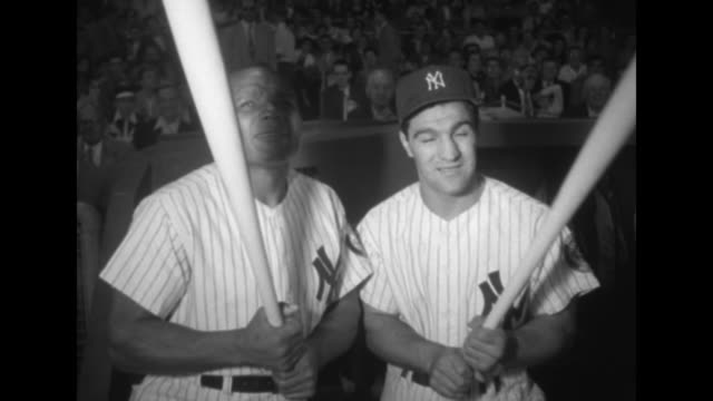 Boxers Rocky Marciano and Jersey Joe Walcott pose in New York Yankees baseball uniforms as they attend game at Yankee Stadium
