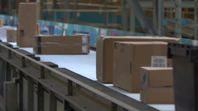 boxes and parcels on conveyor belt at yodel delivery sorting centre hatfield - manufacturing machinery stock videos & royalty-free footage