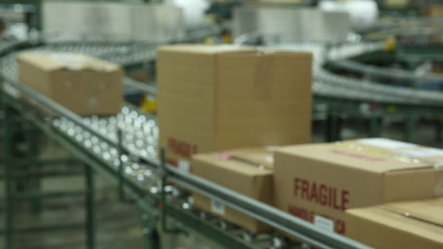 Boxes moving down a conveyor belt for delivery.