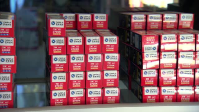 vídeos de stock, filmes e b-roll de cu pan boxes of compact fluorescent lightbulbs on shelf in shili he lighting mall / beijing, china - repetition