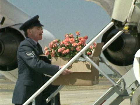 boxes of flowers carried onto queen mother's private jet as she flies to scotland for summer holiday - フットマン点の映像素材/bロール