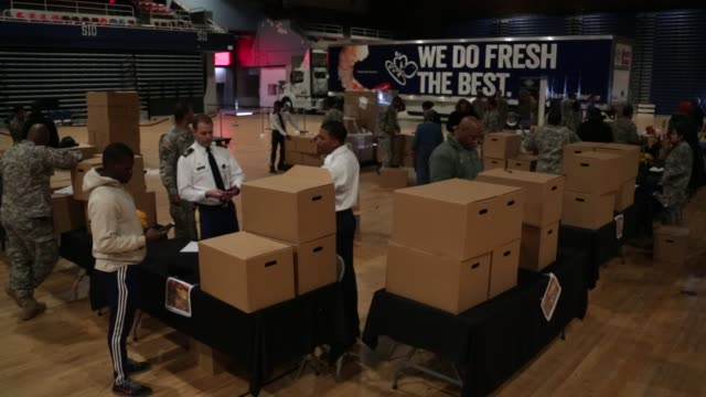 boxes of holiday meal are distributed during an operation homefront event at the dc national guard armory november 23 2015 in washington dc - waffenlager stock-videos und b-roll-filmmaterial