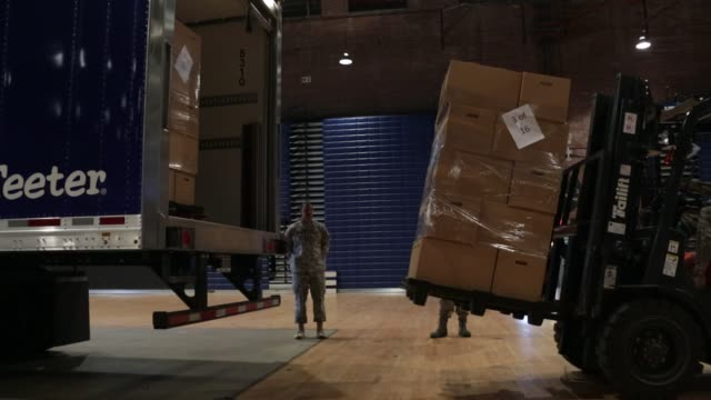 boxes of holiday meal are unloaded from a truck for distribution during an operation homefront event at the dc national guard armory - waffenlager stock-videos und b-roll-filmmaterial