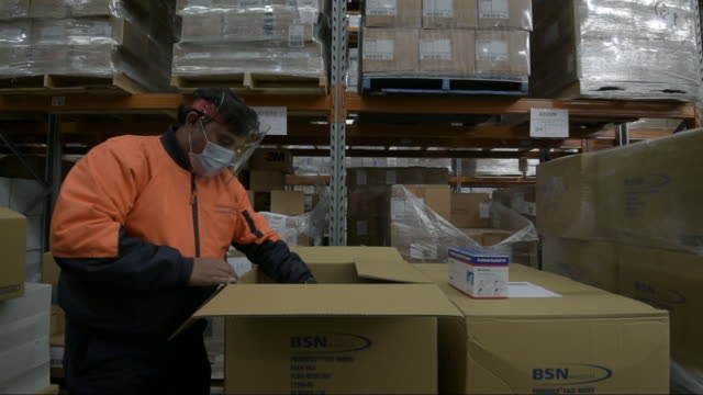 vidéos et rushes de boxes of personal protective wear, health and hospital products are stacked in a government stockpile warehouse in melbourne, victoria, australia, on... - qualité