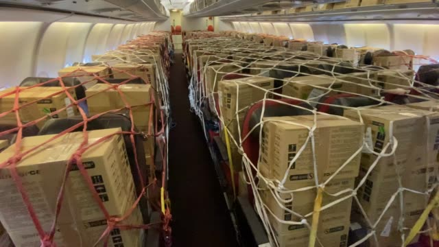 boxes of ppe supplies are strapped to the chairs inside the plane arriving from kuala lumpur, malaysia on the runway at bournemouth airport during... - container stock videos & royalty-free footage