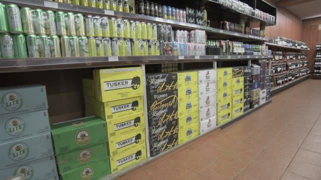 stockvideo's en b-roll-footage met boxes of tusker lager produced by diageo plc sit on shelves inside a nakumatt holdings ltd supermarket in nairobi kenya on saturday feb 18 boxes of... - koffie drank