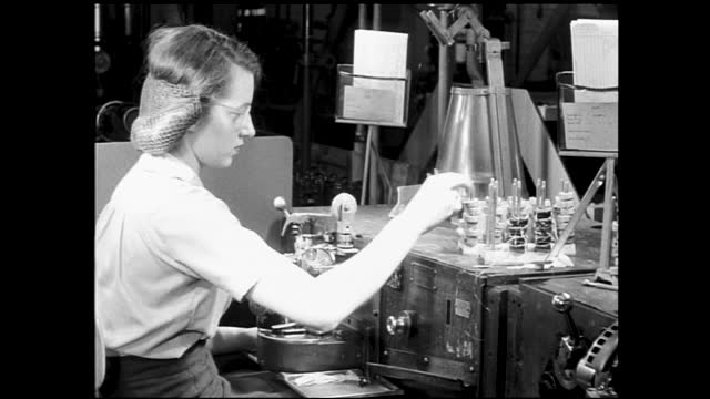 boxes passing by on the conveyor belt inside factory; man adjusting controls; women and men working inside factory on the assembly line and various... - 1940 1949 stock-videos und b-roll-filmmaterial
