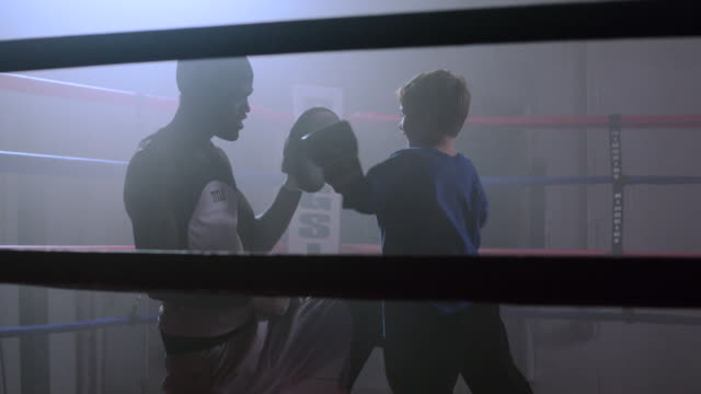 slo mo. boxing coach trains a little boy to box by punching his hands in a boxing ring in a professional gym - instructor stock videos & royalty-free footage