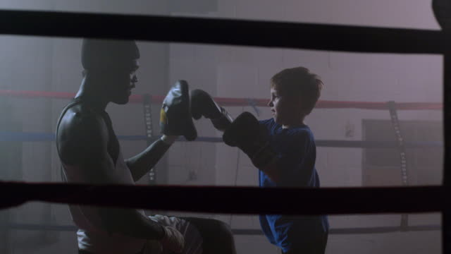 slo mo. boxing coach trains a little boy to box by punching his hands in a boxing ring in a professional gym - ausbilder stock-videos und b-roll-filmmaterial