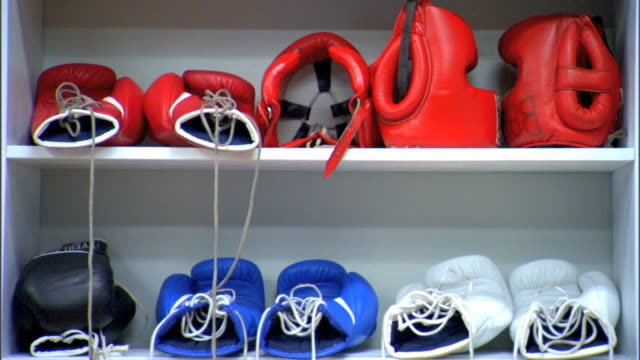 stockvideo's en b-roll-footage met ms boxing gear including gloves of various colors training helmet on shelves in unidentifiable gym lights turning off darkness sports no brands - bokshandschoen