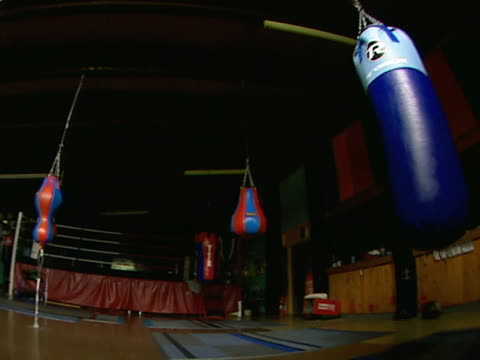 stockvideo's en b-roll-footage met boxing gym lights off w/ hanging speed & heavy bags, practice ring in shadow bg poster and high windows bg - vrijetijdsfaciliteiten
