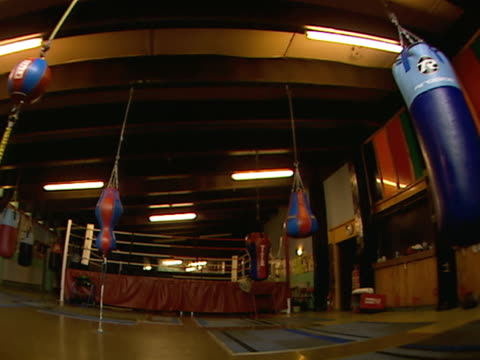 stockvideo's en b-roll-footage met boxing gym w/ ceiling lights off, hanging speed & heavy bags, practice ring bg. ceiling lights turning on. soft focus, row lights turning off. soft... - vrijetijdsfaciliteiten