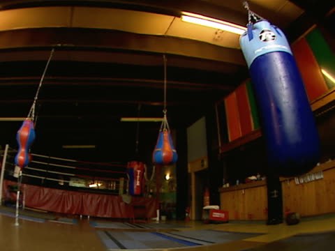 stockvideo's en b-roll-footage met boxing gym w/ ceiling lights off, hanging speeds & swinging heavy bag, practice ring bg. ceiling lights turning on. - vrijetijdsfaciliteiten