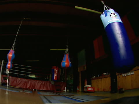 stockvideo's en b-roll-footage met boxing gym w/ swinging hanging speed & heavy bags, practice ring in shadow bg. - vrijetijdsfaciliteiten