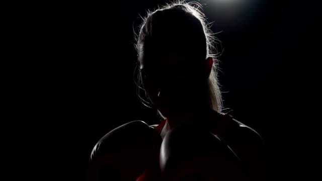 Boxen im Schatten. Mit Schwächen zu kämpfen. Brünette Stanzen ihre Fäuste zusammen