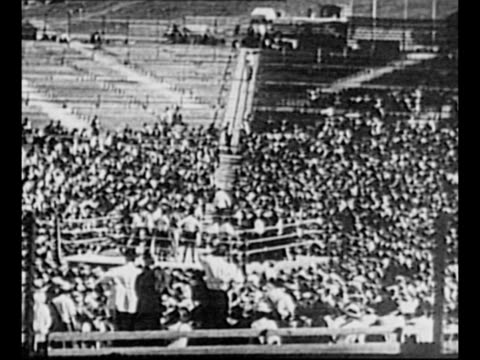 WS boxing match between Jack Dempsey and Tommy Gibbons / LS match in background as spectators watch in foreground / Dempsey applies makeup for an...