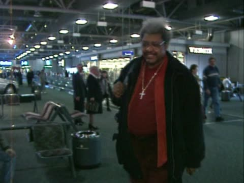 Boxing promoter Don King flies out through Heathrow smiling for cameraman before entering VIP lounge Wears a crucifix around his neck