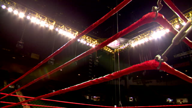 boxing ring corner ropes in empty boxing arena w/ overhead spotlights on, hbo ppv lighted sign in upper room corner. ropes. - 格闘技リング点の映像素材/bロール