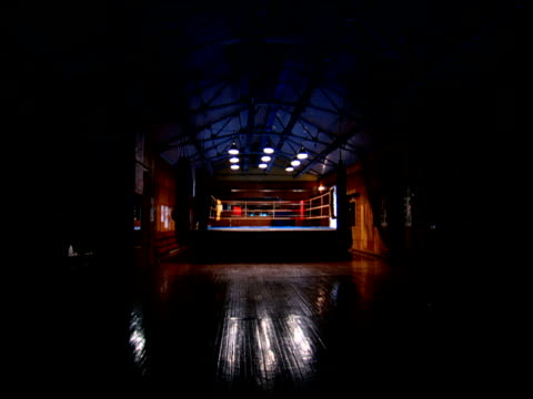 boxing ring in gym is illuminated by fluorescent strip lights russia - ボクシングリング点の映像素材/bロール