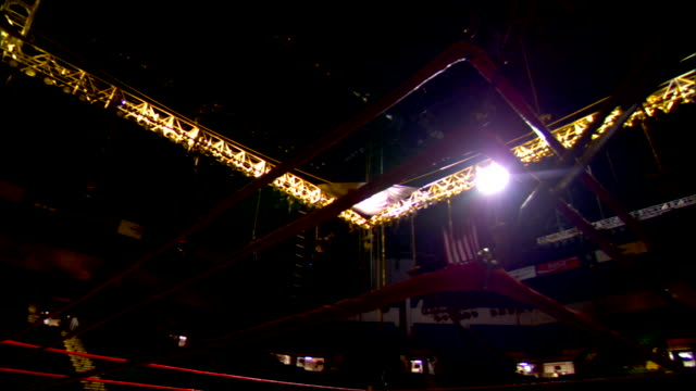 boxing ring ropes in empty arena w/ overhead spotlights on slo pan ring ropes hbo sports lighted sign in upper room corner - ボクシングリング点の映像素材/bロール