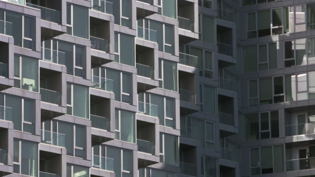 Boxy balconies stacked together create pattern of square and rectangular shapes.