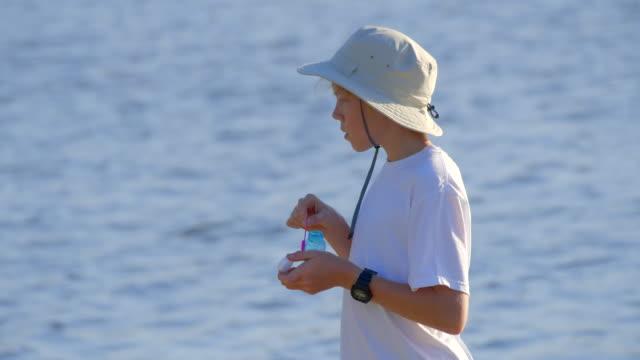 junge 12 jahre alt bläst blasen im park. blaue seewasseroberfläche auf dem hintergrund aus dem fokus. - 12 13 years stock-videos und b-roll-filmmaterial