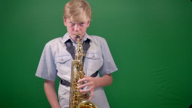 boy 12 years old is playing saxophone in the studio with green chroma-key on the background. - saxophone stock videos & royalty-free footage