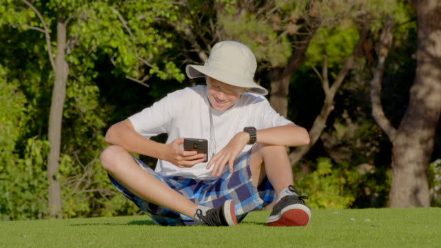 junge 12 jahre alt sitzt auf gras im park und spielt auf mobilen gerät oder tippen von nachrichten. - 12 13 years stock-videos und b-roll-filmmaterial