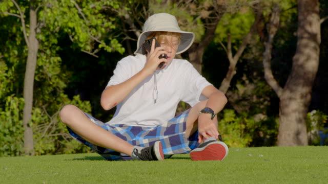 junge 12 jahre alt sitzt auf gras im park und telefoniert. - 12 13 years stock-videos und b-roll-filmmaterial