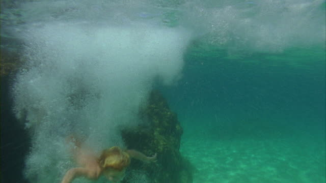 SLO MO, WS, Boy (6-7 jumping off rock into ocean, Oahu's North Shore, Hawaii, USA