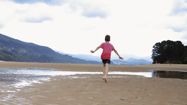 Boy 8-10 years running towards pools at low tide on beach