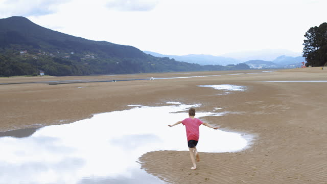WS Boy 8-10 years runs through pools at low tide on beach, he holds arms out like a plane