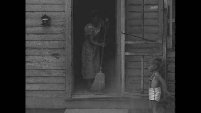 boy about 5 years old in shorts, no shirt and suspenders opens screen door as mother sweeps dust from house out door / note: exact month/day not known - great depression stock videos & royalty-free footage