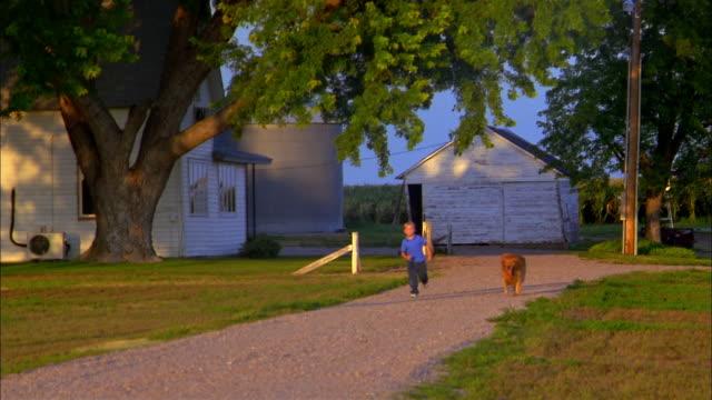 A boy and a dog run down a dirt driveway.