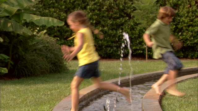 A boy and a girl jump across a fountain in a park.