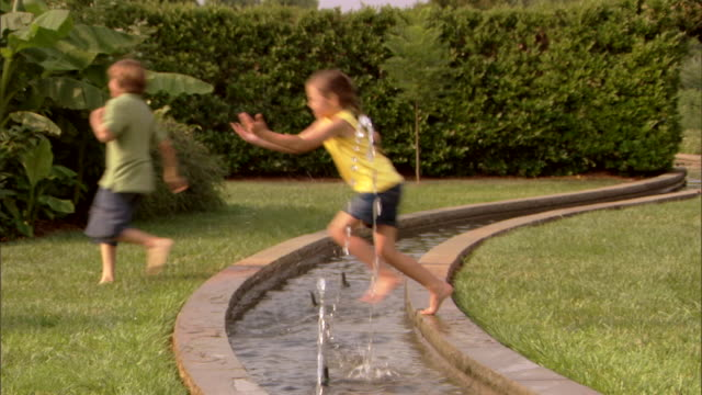 vídeos de stock e filmes b-roll de a boy and a girl jump across a fountain in a park. - 10 11 anos