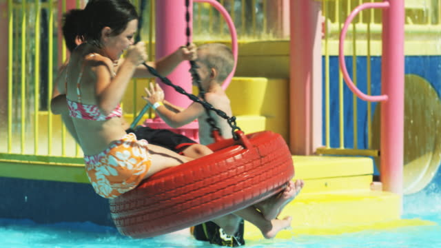 boy and a girl on a tire swing at a water park - tire swing stock videos & royalty-free footage