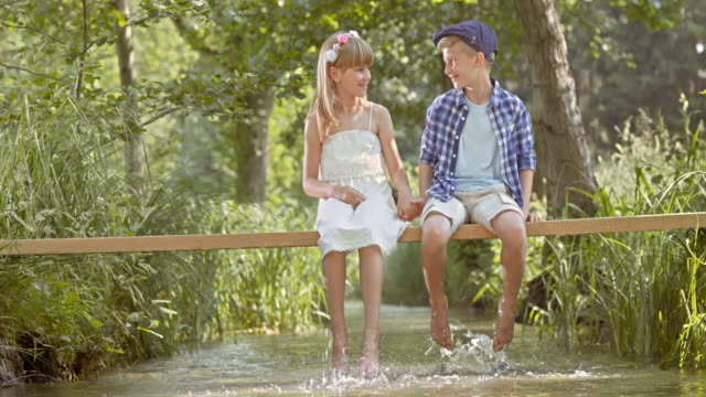 slo mo ds boy and a girl on footbridge splashing water - reed grass family stock videos & royalty-free footage