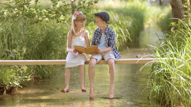 slo mo a boy and a girl sitting on a footbridge and reading - little girls bare feet stock videos and b-roll footage