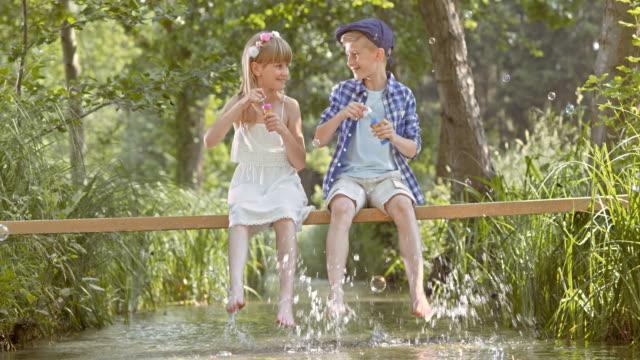 SLO MO TD jongen en een meisje zittend op een voetgangersbrug bellen blazen