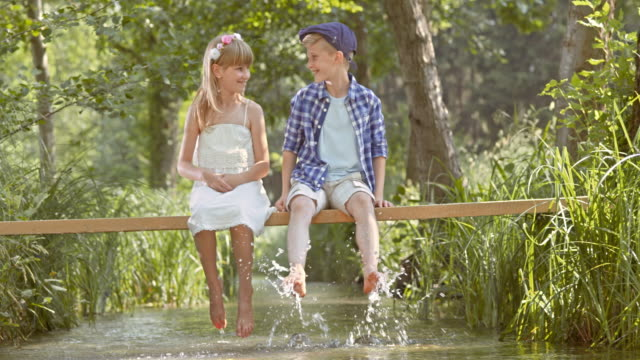 SLO MO A boy and a girl sitting on a footbridge splashing water