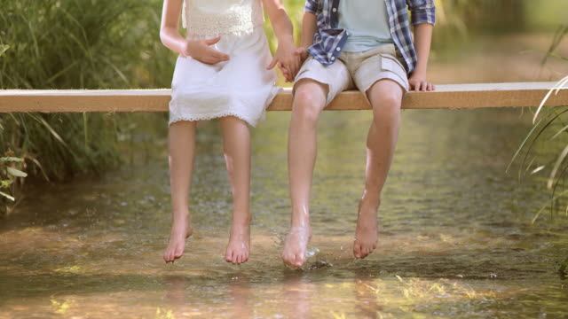slo mo boy and a girl sitting on a footbridge splashing water with their feet - little girls bare feet stock videos and b-roll footage