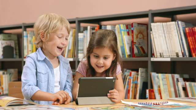 DS Boy and a girl using a tablet sitting in a public library
