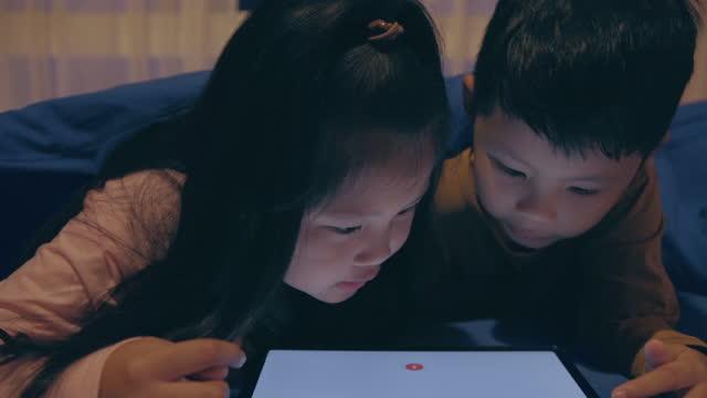 vidéos et rushes de un garçon et une fille utilisant la tablette sous la couverture la nuit - digital tablet