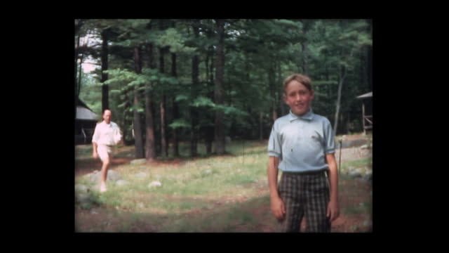vidéos et rushes de 1966 boy and dad approach camera in the woods - camping