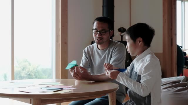vidéos et rushes de boy and father making paper planes together - origami
