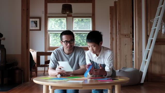 boy and father making paper planes together - day in the life stock videos & royalty-free footage