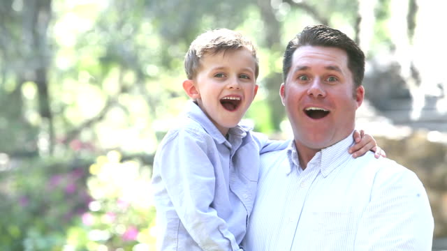 Boy and father outdoors, happy and surprised